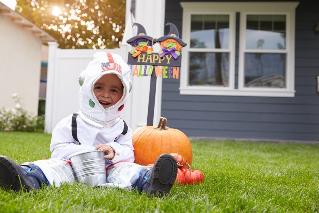 Boy Dressed In Trick Or Treating Spaceman Costume On Lawn